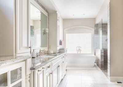 Large bathroom in luxury home with two sinks, tile floors, fancy cabinets, large mirrors, and bathtub